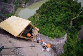 صدق ولا تستغرب .. متجر معلّق على ارتفاع 330 قدمًا يبيع الماء والعصائر لمتسلقي الجبال جنوب الصين